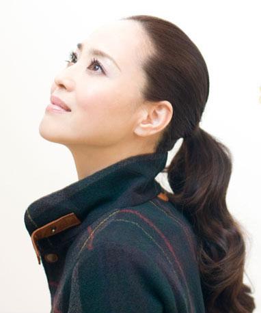 髪の毛を一つにまとめて上を見つめる松田聖子