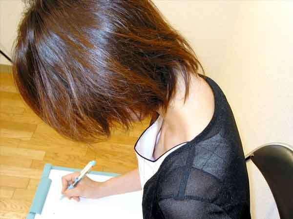 書類を書いている女性、上から見ると服の間からブラジャーが
