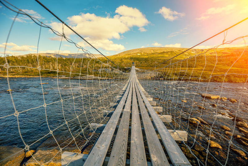 storyblocks-hanging-bridge-over-mountain-river_BIzcE5Id1z