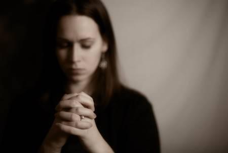 11936302-彼女の手を一緒に祈って、ブルネットの女性