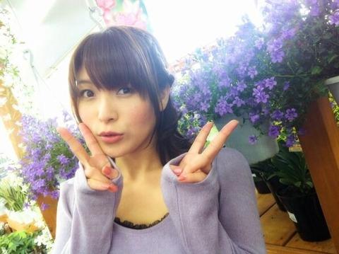 紫のお花を前に微笑む新田恵海