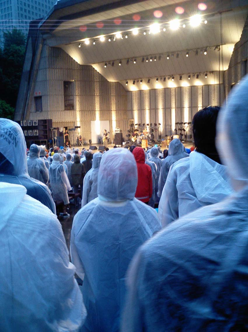 ピーズ 何かの宗教みたいな白装束雨具集団。野音は雨降ると儲かるね!雨具売れるか...  rewデ