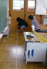 巻尺で教室の長さを測る児童
