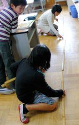 竹尺で教室の長さを測る児童
