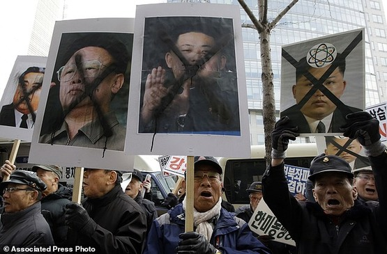 South_Korean_protesters_shout_slogans_as_they_hold_the_photos