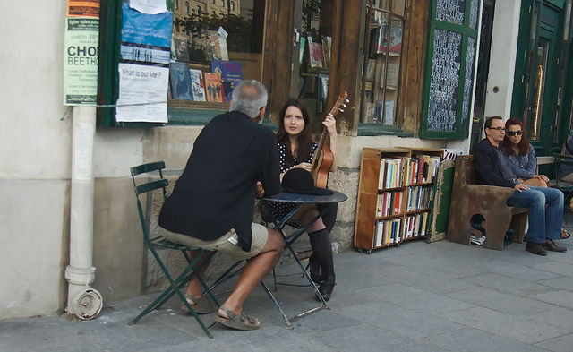A girl playing guitar in front of an antique shop By Marcel