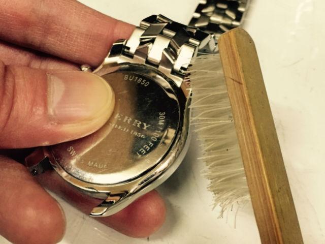 腕時計の裏蓋周りの汚れやホコリをブラシで除去します