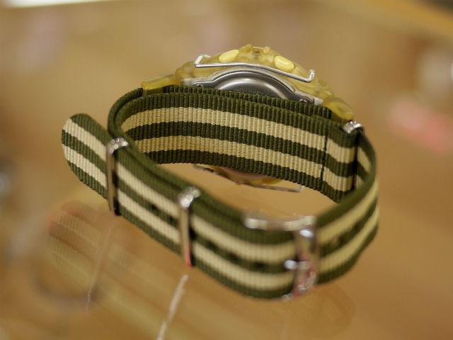 NATOタイプの引き通しの腕時計ベルト。カーキ色のストライプ