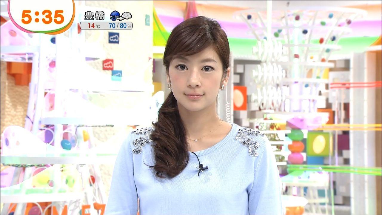 ビジュー付きの水色のセーターを着てカメラを見つめるアナウンサー、生野陽子