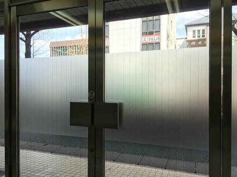 テナントガラス面にシート文字の設置作業