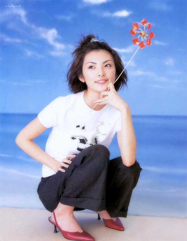 風車を手に持って膝を曲げて座る田中麗奈