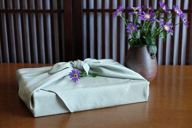 風呂敷包みと都忘れの花