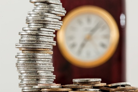 時計と積み重なったコイン(硬貨)