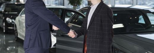 お客さんと握手する自動車販売店のスタッフ