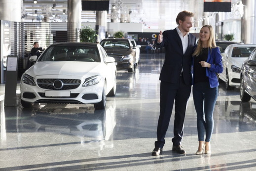自動車販売店の展示場を歩くカップル