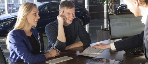 自動車を商談中のカップル