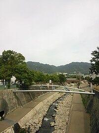神戸市内六甲山を背に、初夏の川沿い。