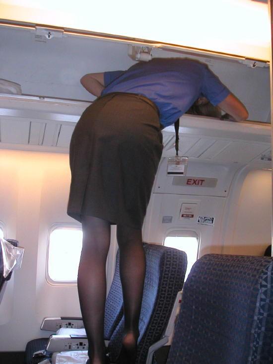 飛行機の座席に登って荷物棚を確認するスチュワーデス