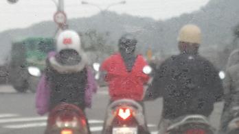 カッパを前後逆に着る台湾女性