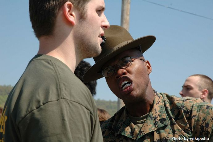1280px-Marine_Corps_drill_instructor_yells_at_recruit