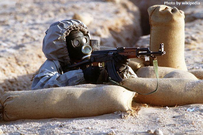 1280px-Syrian_soldier_aims_an_AK-47