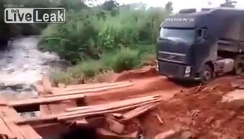 今にも崩れ落ちそうな木製の橋を渡るトラック