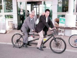 タンデム自転車にまたがる両県の知事