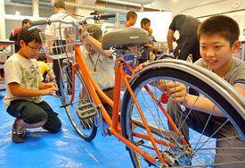 自転車のパンクを修理する小中学生