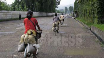 取締りを避けるために裏通りを疾走するコメ商売の女性たち