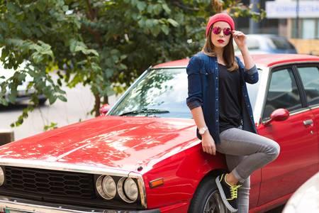 65425932-赤いレトロな車のそばに立って非常にスタイリッシュな女性