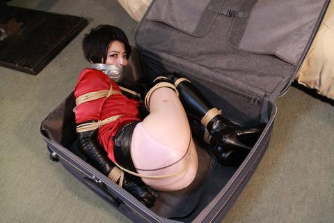 キャリーケースに閉じ込められるサテンブラウスの美女