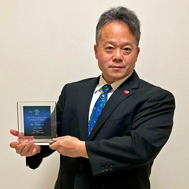 Dr. MaCHO Holding the Award Plaque