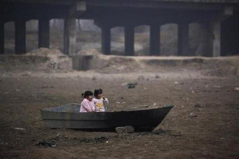 水のない河に残された舟で遊ぶ