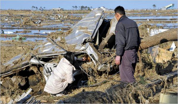スクールバスの残骸に閉じ込められた娘の死体を撫でる両親(宮城県山元町)