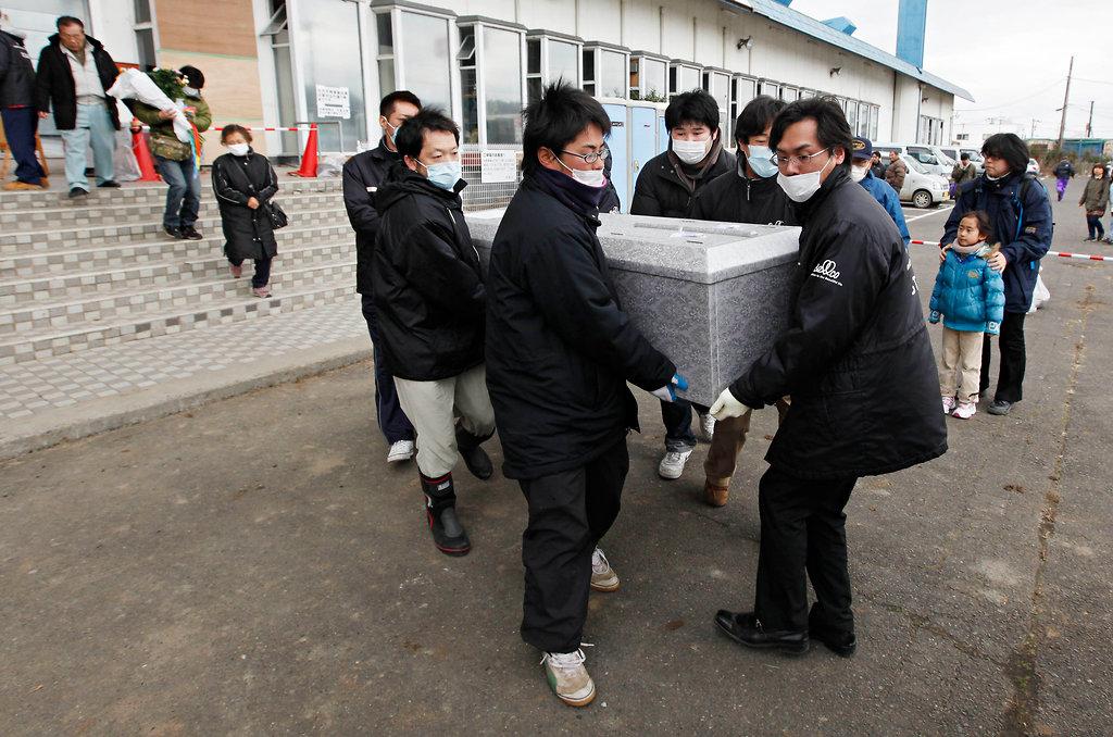 遺体安置所となったボーリング場から運び出される棺(宮城県名取市)