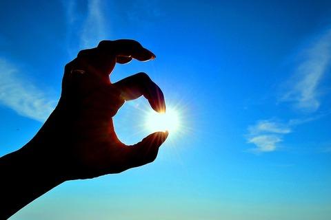 指の向こうに見える太陽