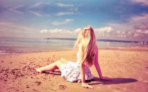 Woman-Sitting-on-the-Beach-Sand-600x375