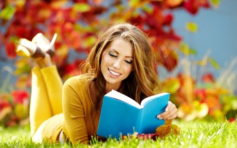 Girl-Sitting-on-Green-Grass-and-Reading-Book-600x375