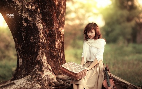 Girl-with-Violin-Sitting-Next-to-Tree-600x375