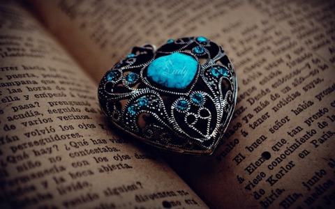 Antique-Heart-with-Blue-Stone-in-the-Middle-of-Open-Book-600x375
