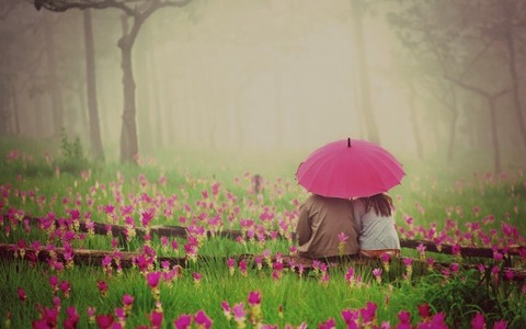 Couple-Sitting-At-The-Park-With-Umbrella-600x375