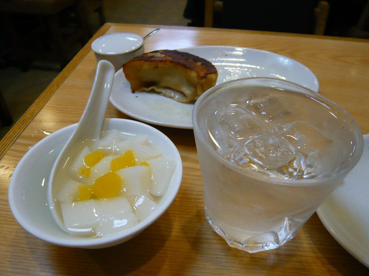 大きなグラスに注がれた焼酎400円とサービスの杏仁豆腐