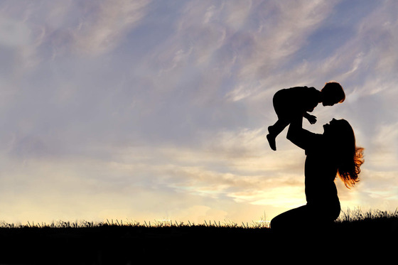 silhouette-of-happy-mother-playing-outside-with-baby