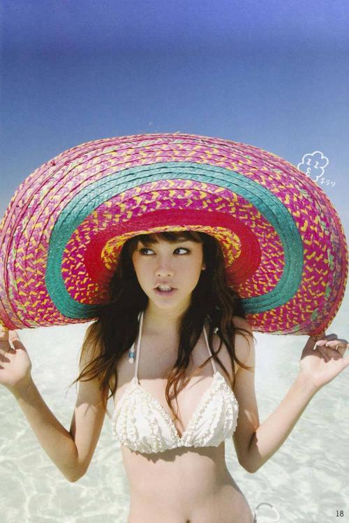 綺麗な海の前で大きな帽子を被って桐谷美玲