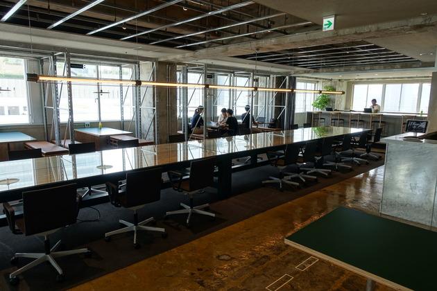 入ると中央に長テーブルが置かれたフリースペース。窓が大きい&多いのでわずかな電球でもすごい明るさ