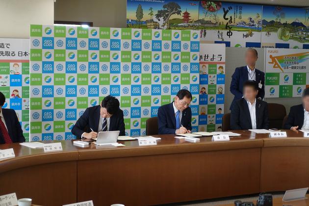 ジオコード代表取締役の原口(左)と静岡県袋井市の原田市長(右)が連携協定書に調印をおこない、、、