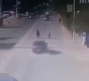 親子が道を渡ろうとするが、猛スピードの車が子供だけ撥ね飛ばしてしまう