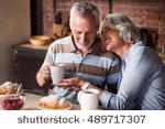 stock-photo-happy-old-couple-having-coffee-together-489717307