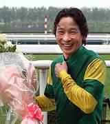 花束を手に笑顔を見せる安藤騎手