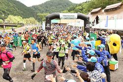 住民やスタッフとハイタッチしながら走り出すロングコースの参加者=南砺市利賀村上百瀬の利賀国際キャンプ場